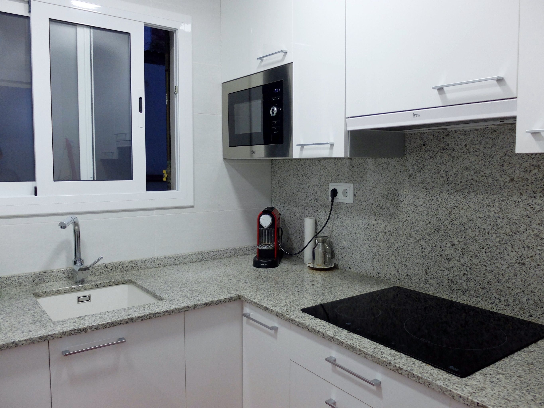 Reforma de cocina con encimera de granito y muebles for Encimeras de granito blanco