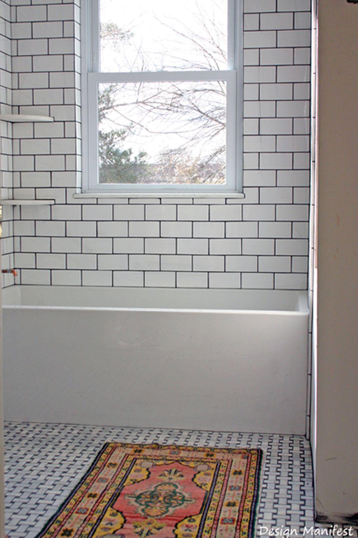 Dark grout unites the white subway tile tub surround and ...
