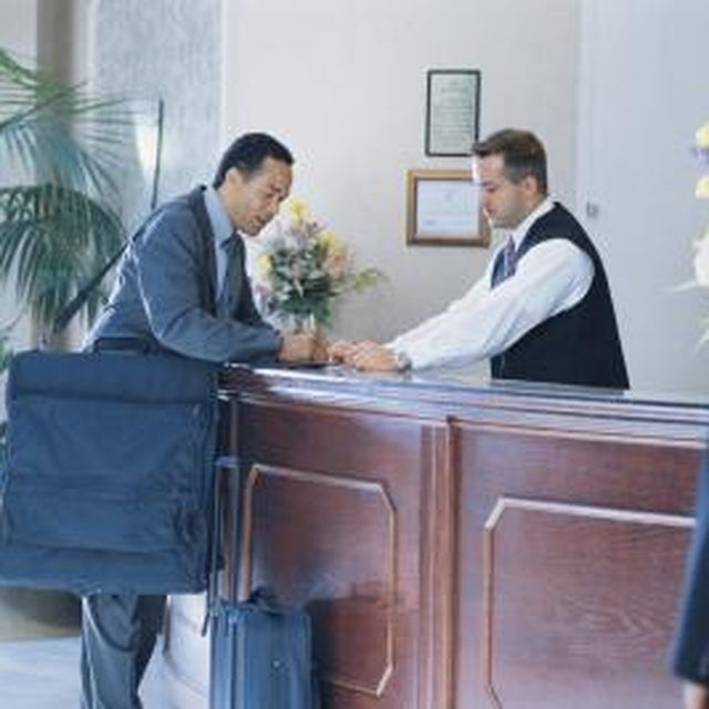 Hotel front desk clerk helping a businessman check in to hotel - hotel interview questions