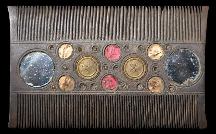 Wooden Comb inset with Foil-Backed Glass Roundels | Northern India or Afghanistan | circa 1900 | This H-comb of slight lentoid form has been cut from a single piece of light, dark wood. One side is cut with fine teeth; the other with slightly courser teeth. The middle section, which functions as the grip, is decorated with multiple circle motifs inset with mirrored glass, coloured foil, beads, and incised brass roundels (some losses). | The Jen Cruse Collection