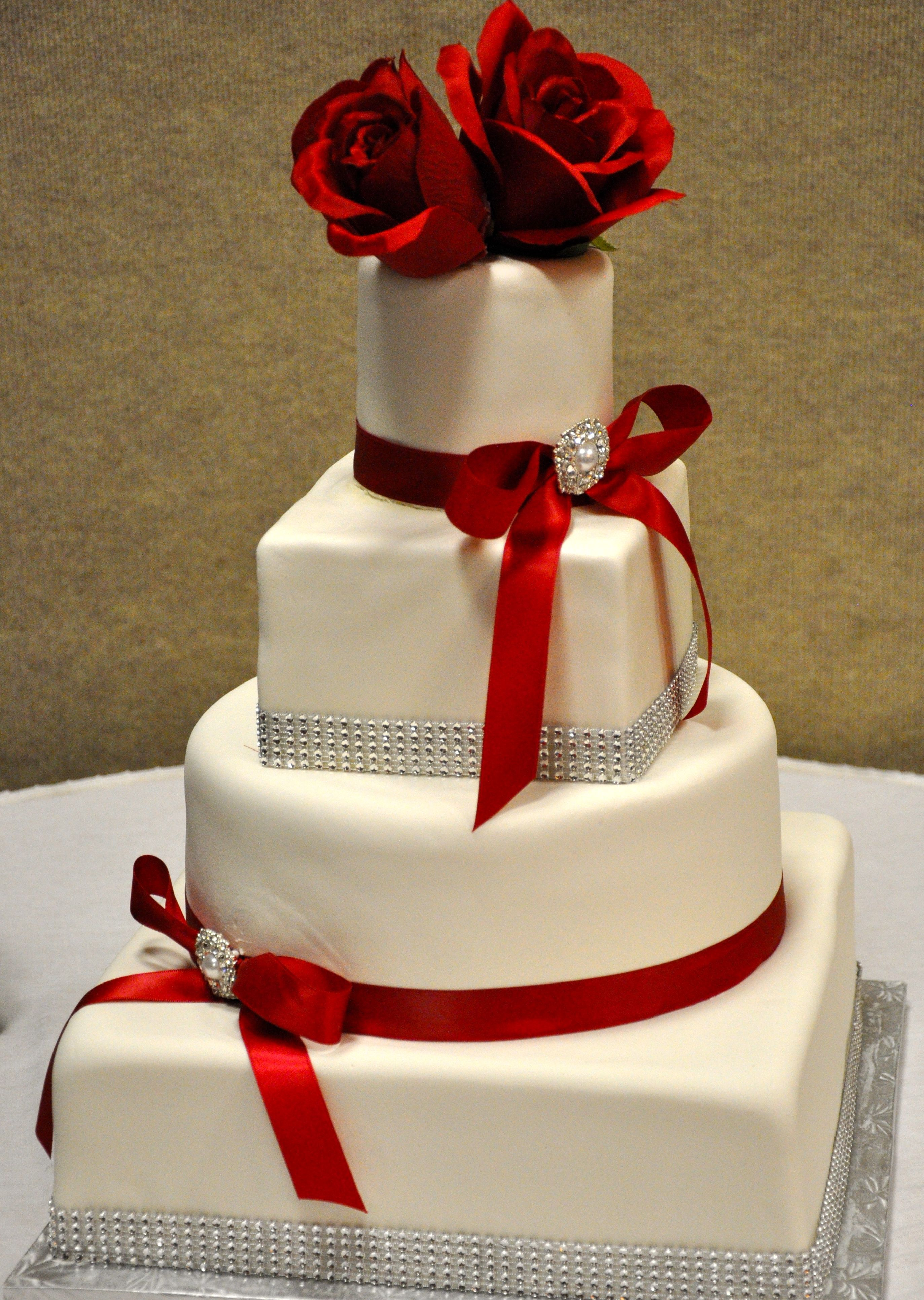 Three Tier Wedding Cake With Red Flowers And Red Ribbon