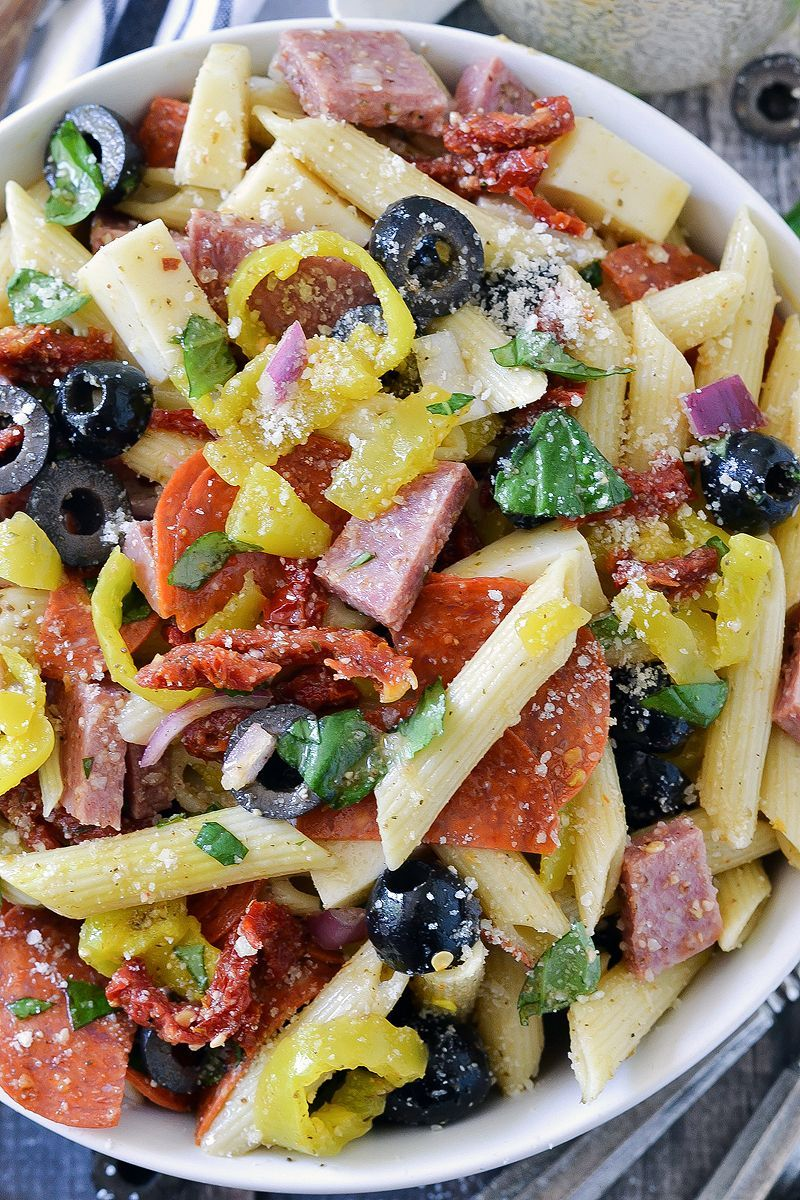 Pasta Salad This Italian Pasta Salad is loaded with salami, pepperoni, cheese, sun-dried tomatoes, banana peppers, olives, basil, and tossed in an easy dressing!This Italian Pasta Salad is loaded with salami, pepperoni, cheese, sun-dried tomatoes, banana peppers, olives, basil, and tossed in an easy dressing!