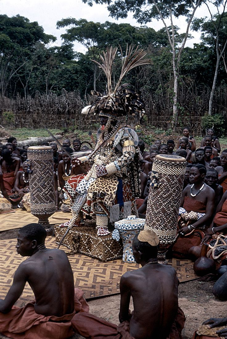 Africa   Nyim Kot a-Mbweeky III wearing royal dress 'Bwaantshy'; royal headdress known as 'Ntshuum Aniym'; necklace 'Lashyaash' made of leopard teeth; sword 'Mbombaam'; lance 'Mbwoom Ambady'; drums of reign 'Pelambish'; basket 'Kweemishaam'l' and other items of royal adornment.  DR Congo, 1971   ©Eliot Elisofon