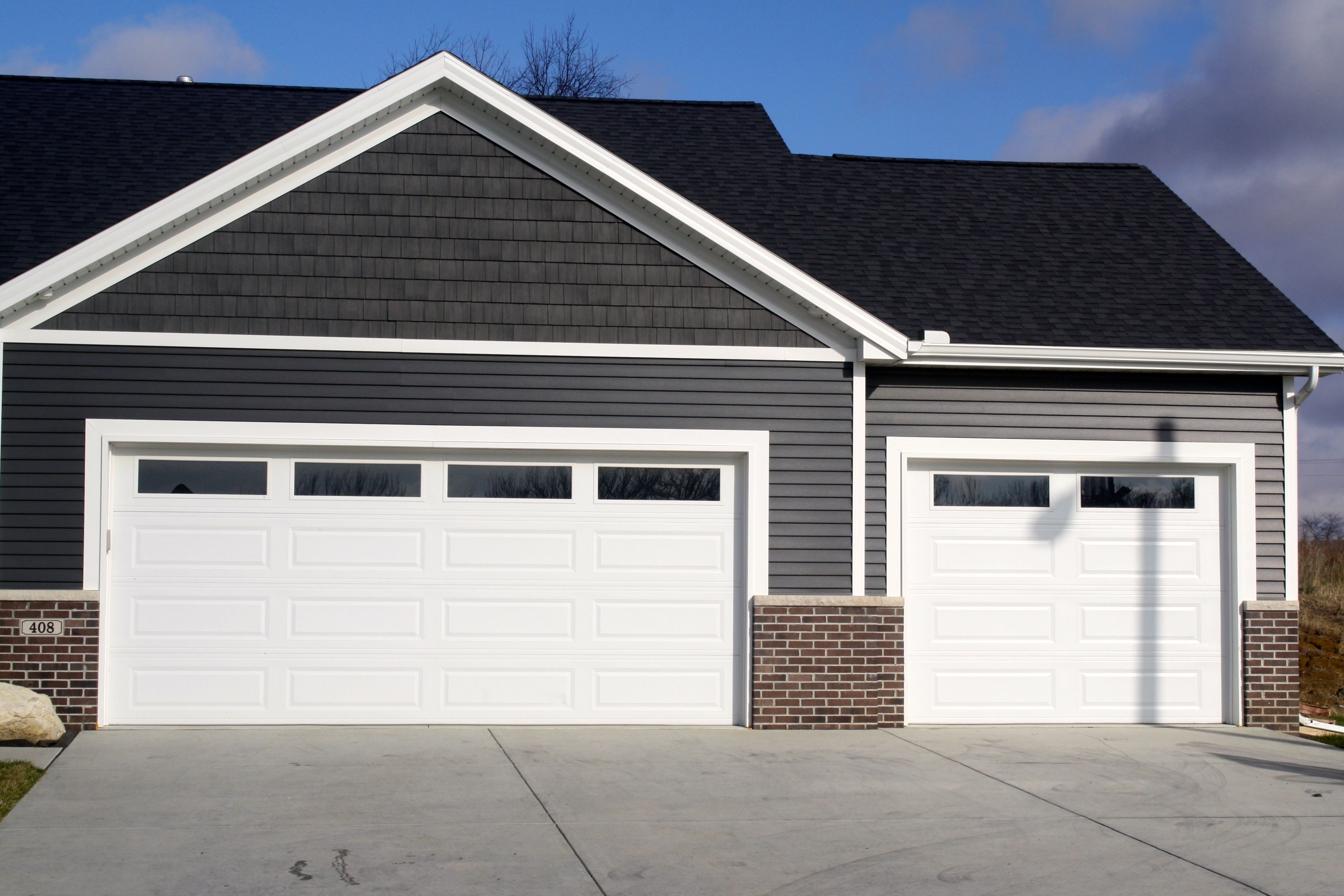 Two White Garage Doors With Plain Glass Inserts In Red