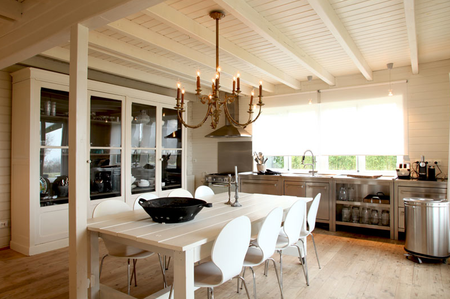 White roller shades let light in while adding a modern touch in this chic French country style kitchen.