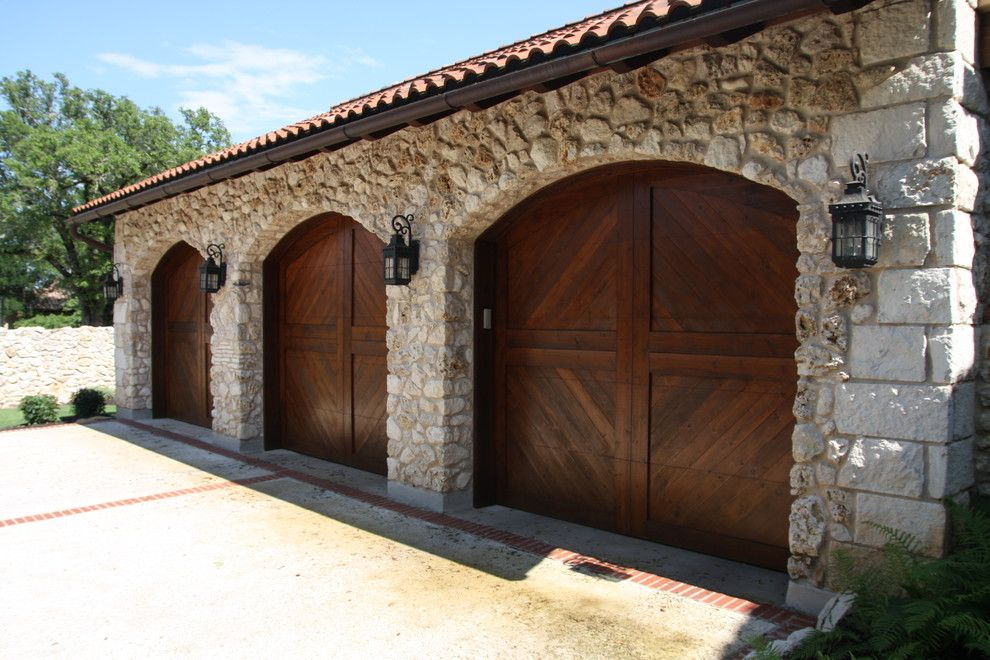 A Rustic Mediterranean Stone Garage With Heavy Wooden Doors