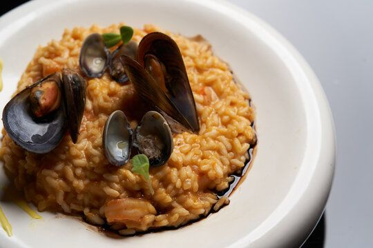 Risotto with mussels and rice in a white plate. Spanish cuisine, Seafood Paella - Buy this stock photo and explore similar images at Adobe Stock