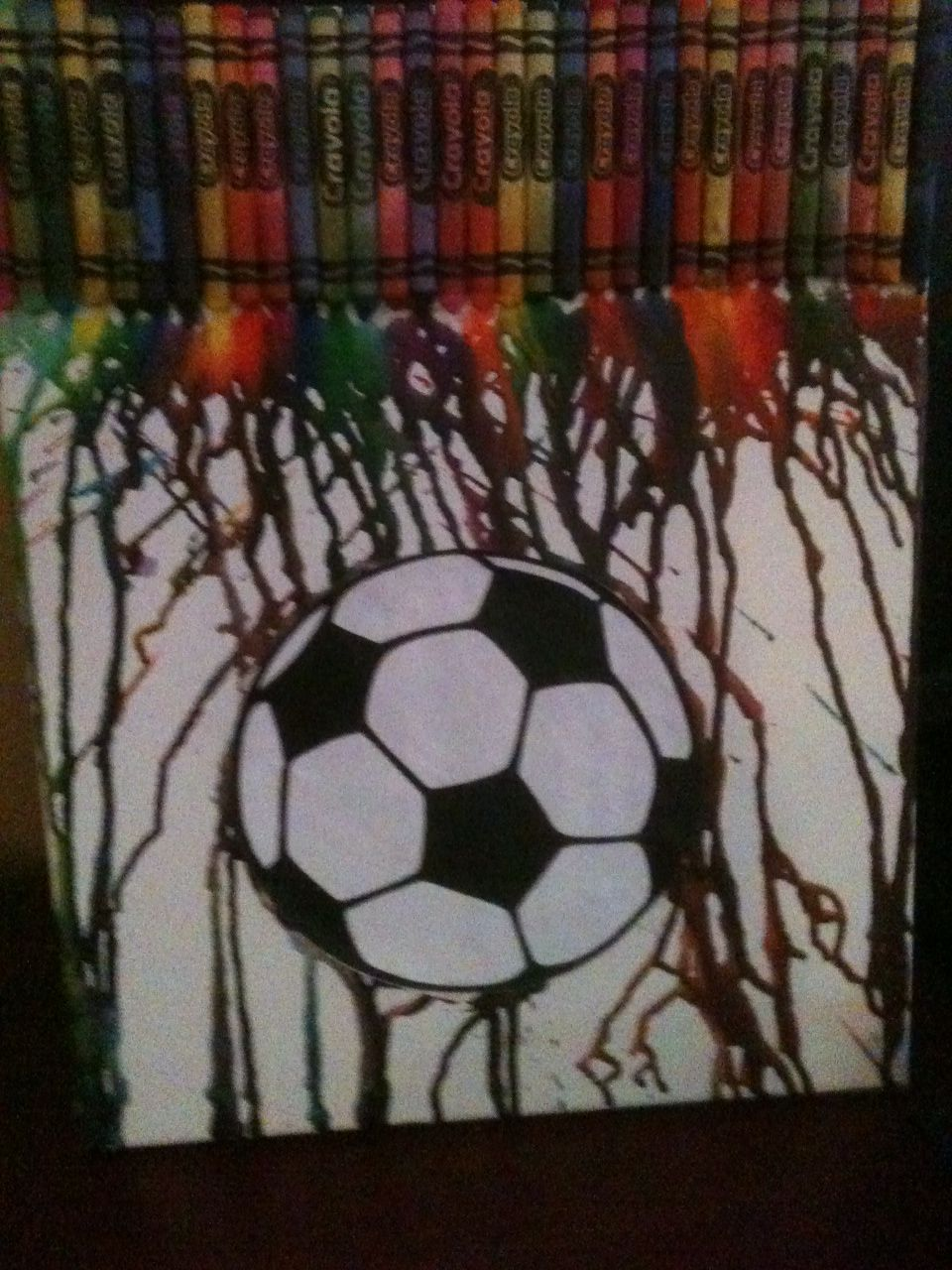 Craft #16 - melted crayons on canvas.  She REALLY liked this one.  Tried to use some parchment paper to create a circle void in the middle - but that didn't work very well for her.  She glued a soccer ball cut out onto where the void should have been.