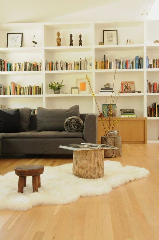 The simple arrangement with the wooden stump and the lambskin rug opens the room up so nicely. Also love the idea of the wooden stump as side table!