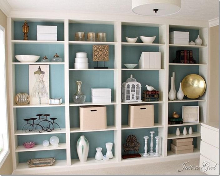 DIY bookshelves from Ikea made to look like built ins over a stunning blue  wall!