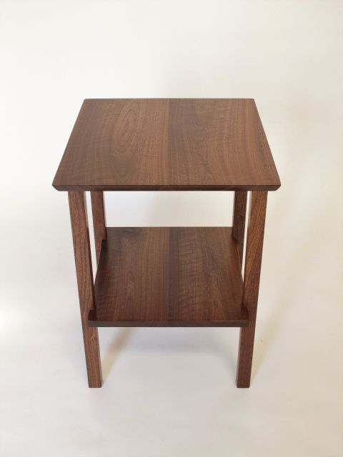 A solid walnut end table with shelf the space between the top and shelf is