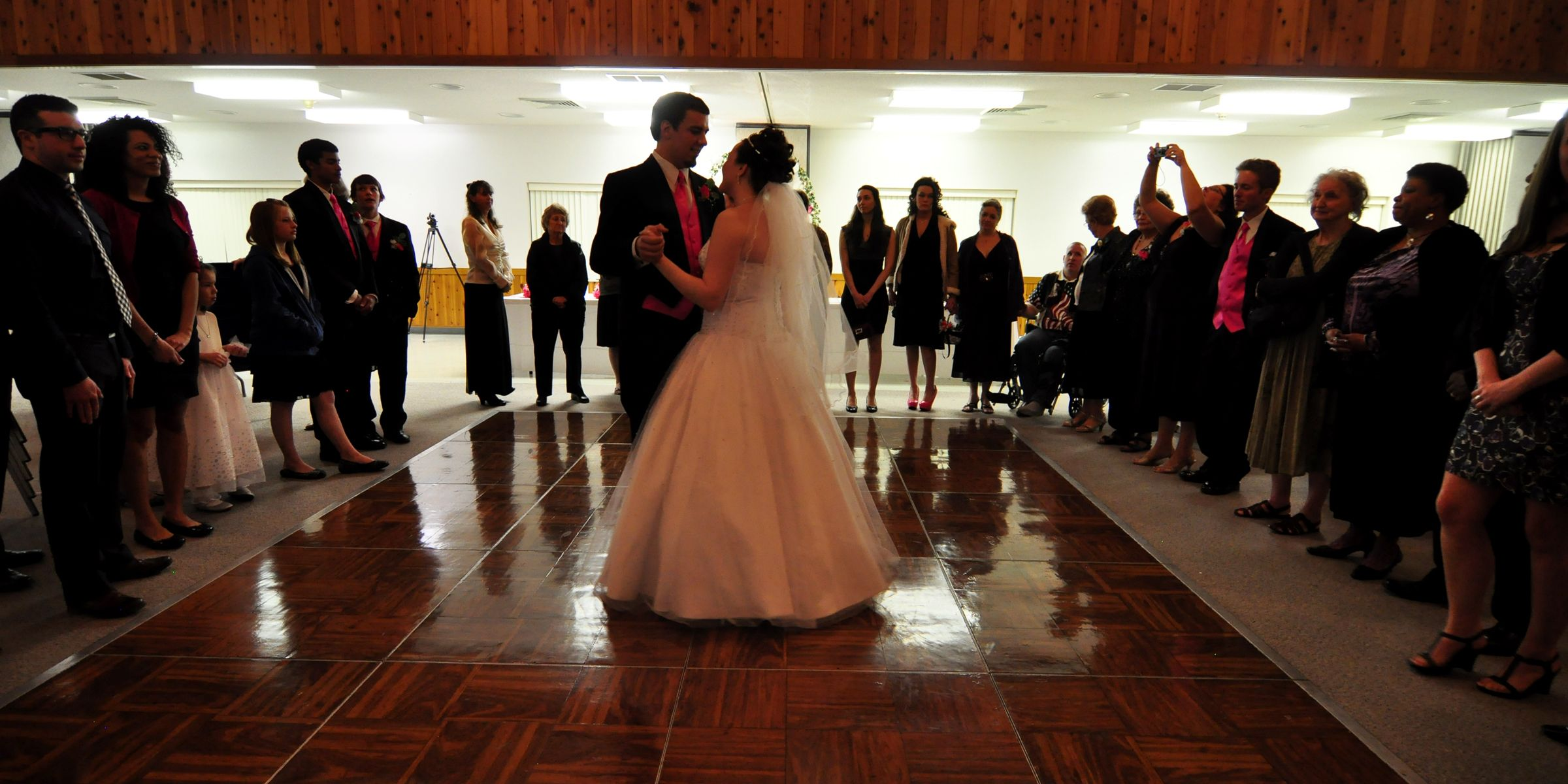 Wedding photography idea: available light dance photo with crowd encircling couple
