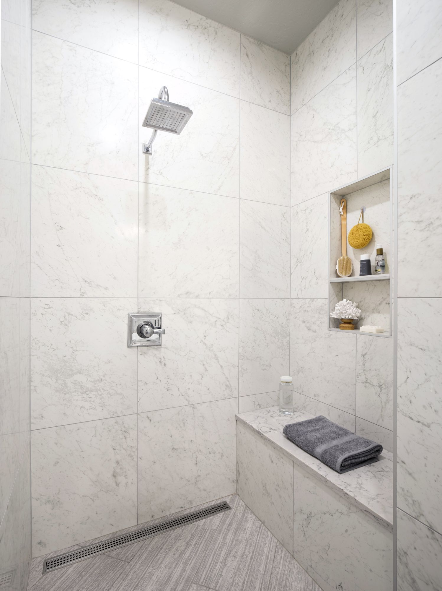 This curbless shower was created with faux-marble porcelain tiles on ...