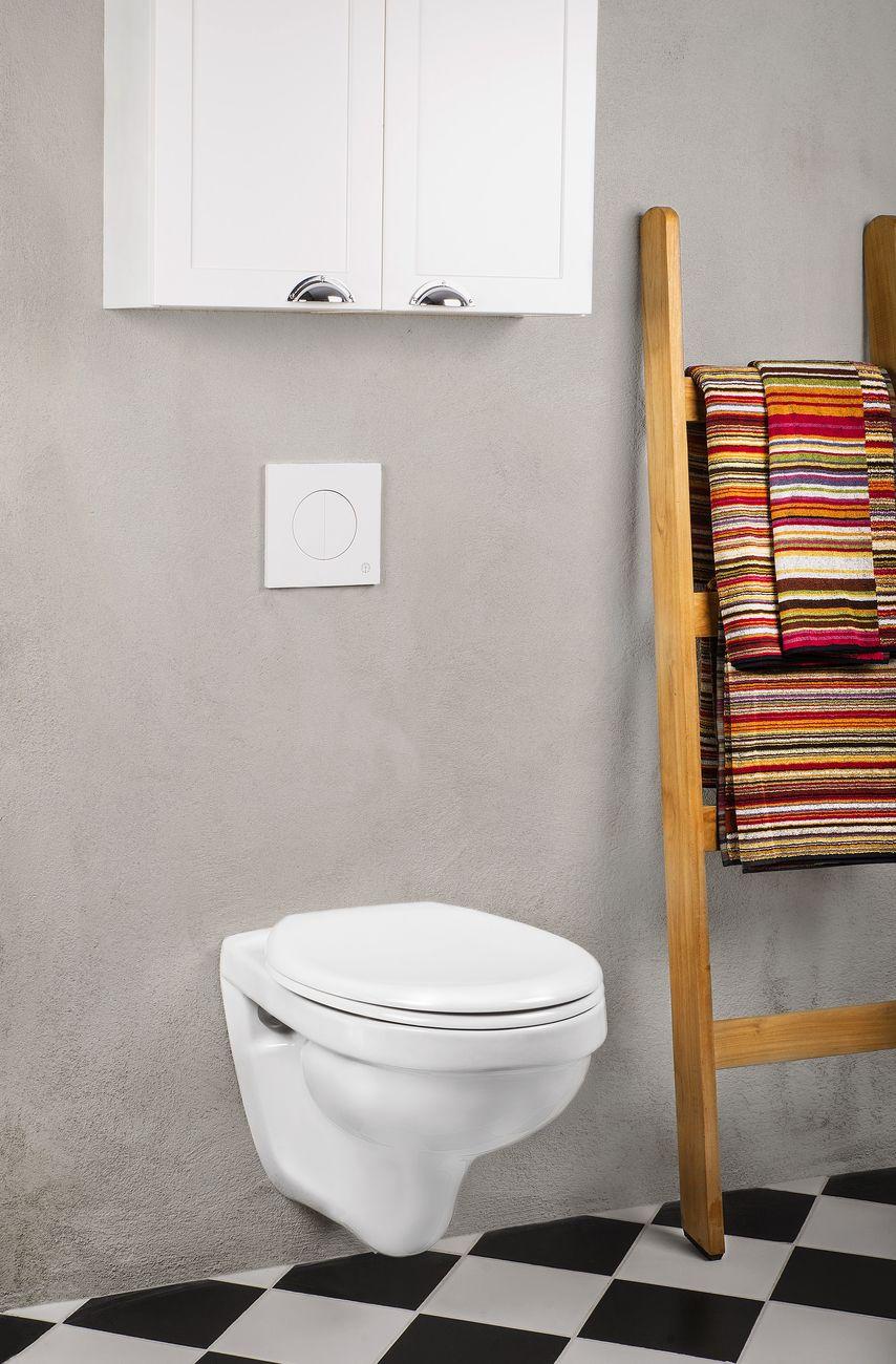 Snålspolande, vägghängd toalett med spolknapp i vitt glas pryder ...