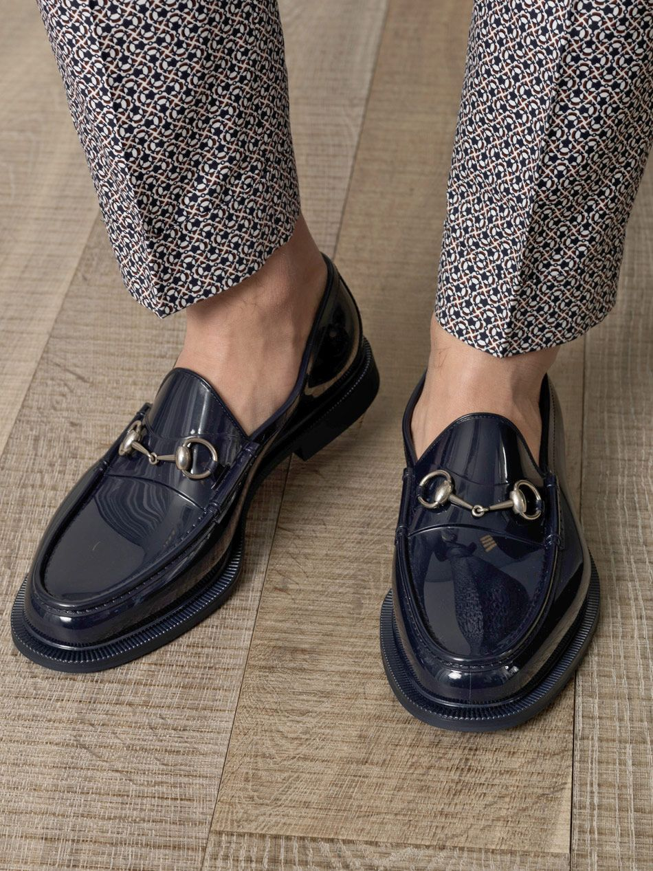 Navy-blue slip-on metal detail loafers. The label's warm ...