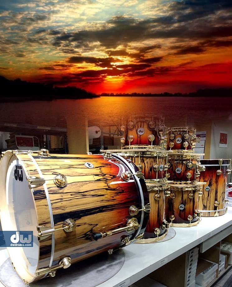 very nice art of a real set of drumkit pieces including huge bass drum with red and yellow brown paint coloring to match the sunset colors beyond the
