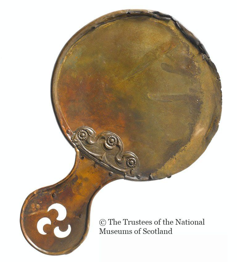 """Balmaclellan mirror; National Museum of Antiquities, Edinburgh, UK. """"Bronze Circular Mirror, measuring 13 inclies in length including handle, with embossed ornaments on each side, and handle ornamented with triple perforation; a Crescent-shaped Plate of Bronze, ornamented with incised scroll patterns its greatest diameter measures 13 inches, and across the plate 2 inches.1st century BC — mid 1st century AD Southwest Scotland."""