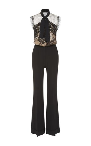 This sleeveless **Elie Saab** jumpsuit is rendered in crepe cady with double georgette and features a nude lace bodice with a scarf neck and a flared pant with folded cuffs.