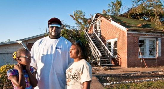Caitlin Moore, Tracy Sturdivant, and Tiffaney Sturdivant stand in front of their former home. The April 2011 tornado that roared through Tuscaloosa, Alabama, did severe damage to it. Now, the family lives in a 3-bedroom house with Tiffaney's mother and stepfather. (Photo: Laura Reinhardt/World Vision) #WorldVision