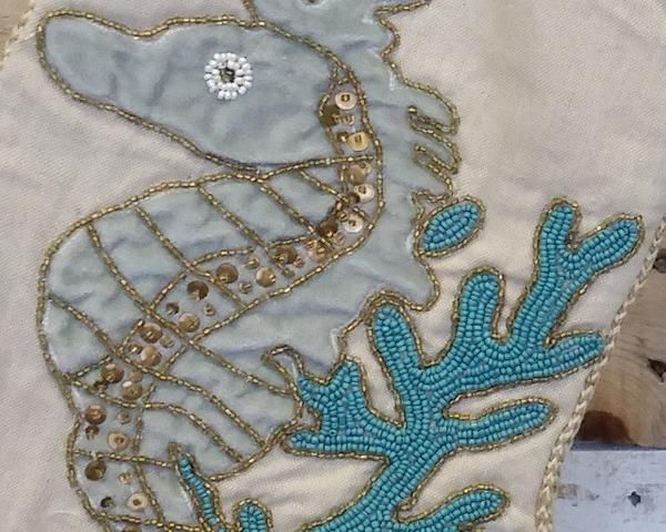 Stunning velvet applique sea creatures detailed with beading in gold and aqua. Braided trim finishes off the high style nature of the Saltwater Serenity Christ