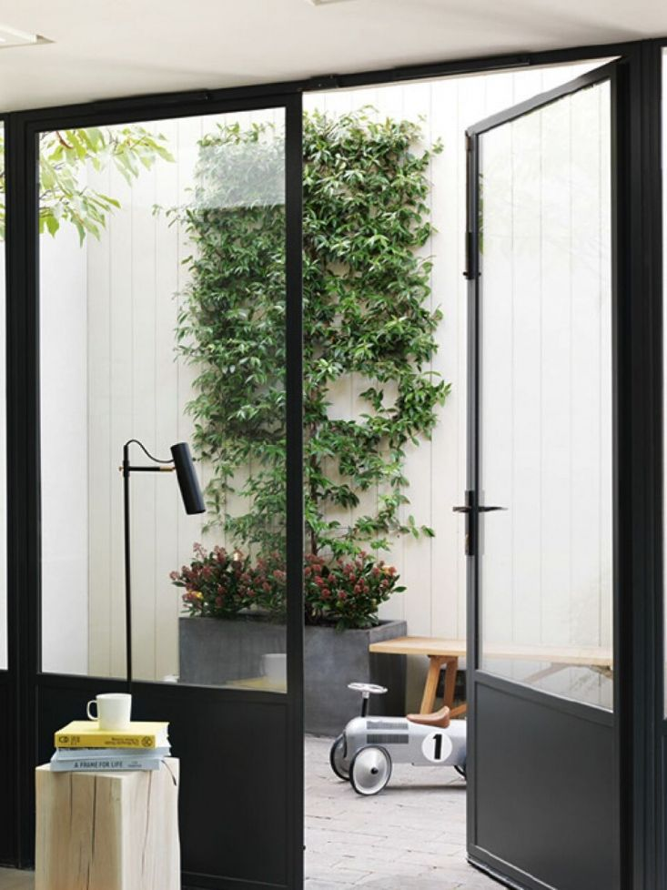 Steel-framed glass doors open to a courtyard in a remodeled …