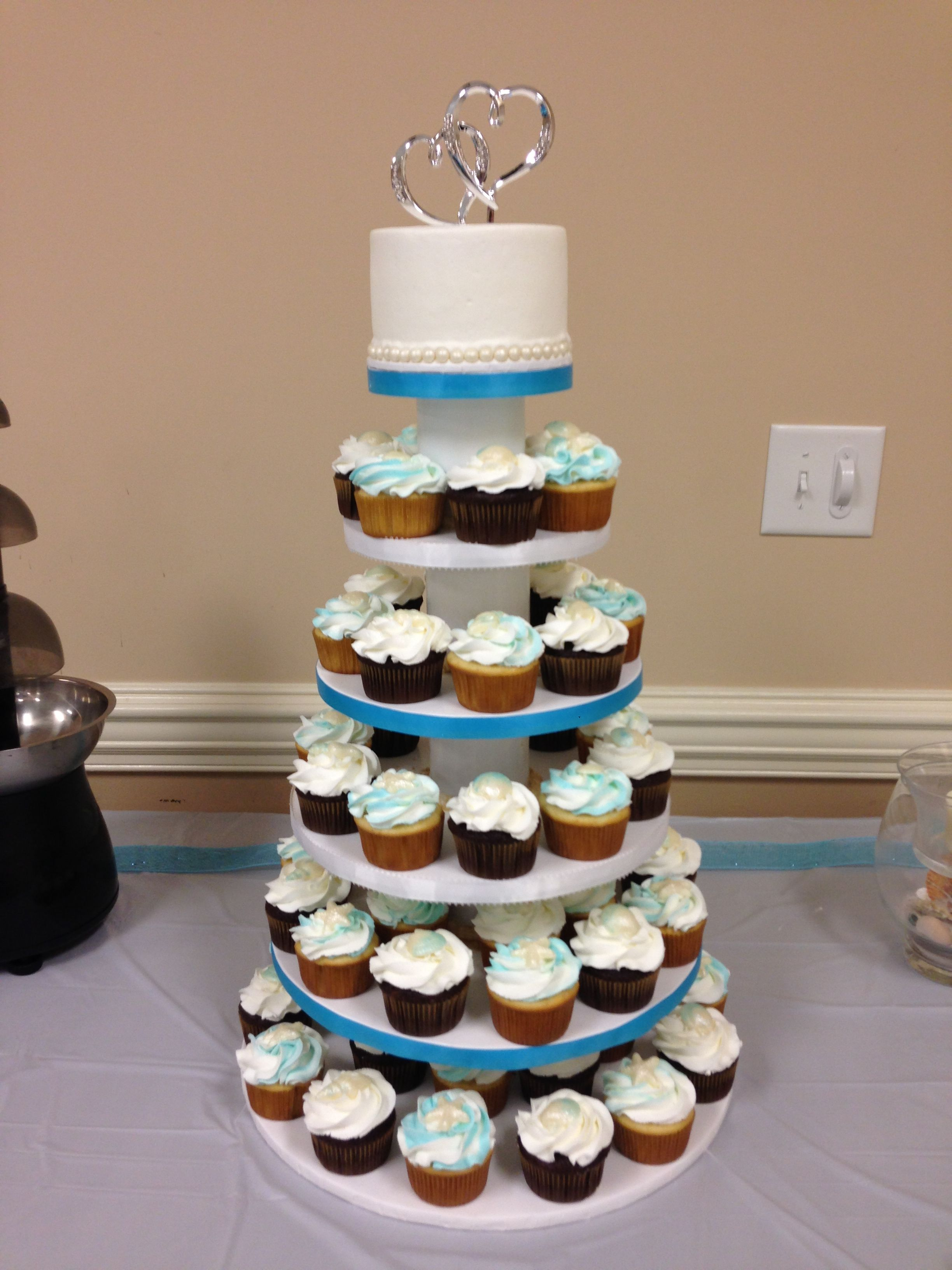Beach themed wedding cupcake tower. Wedding cupcake tower is 6-8-10-12-14-16. Held small 5 inch cake for 1st anniversary and 64 cupcakes with white chocolate shells.
