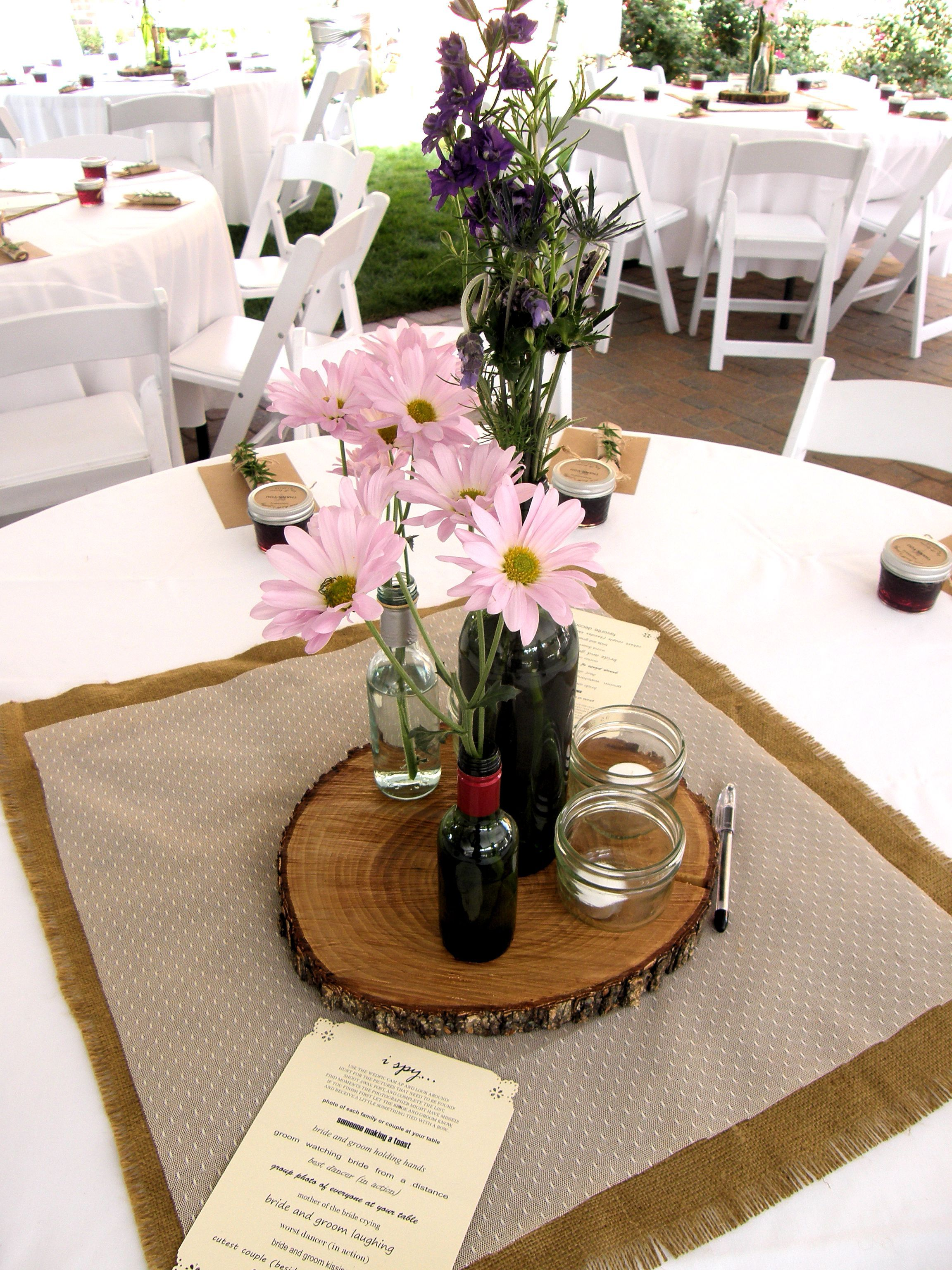 Wooden slab centerpieces with old wine bottles labeled