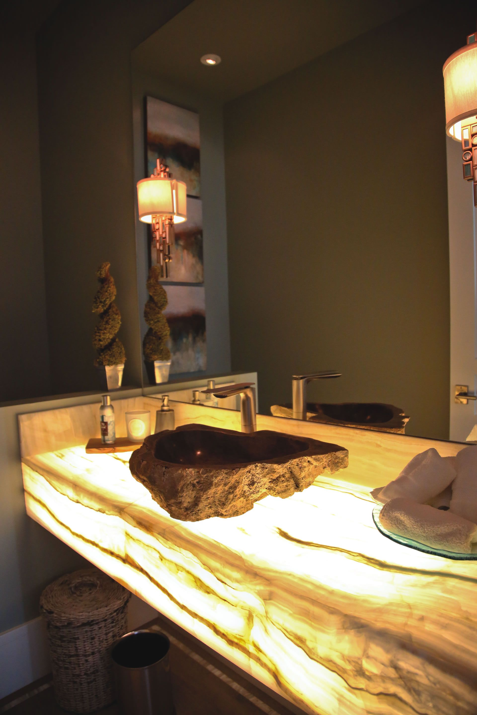 LED light shines through a white onyx countertop, illuminating the  petrified wood sink above it