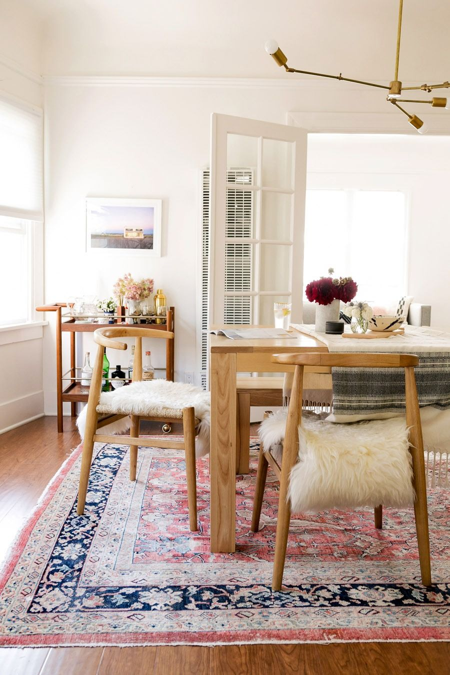 John vogel chairs from west elm sheepskin create a modern bohemian dining room in this photographers los angeles home