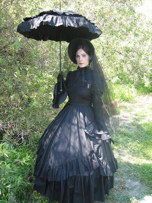 A great picture of Jackie dressed in our Long Mourning Dress, Hoop Petticoat and the Long Black Cotton Bustle Skirt. Paired with a parasol and bonnet, she makes the perfect Victorian Lady mourning for her loved one.