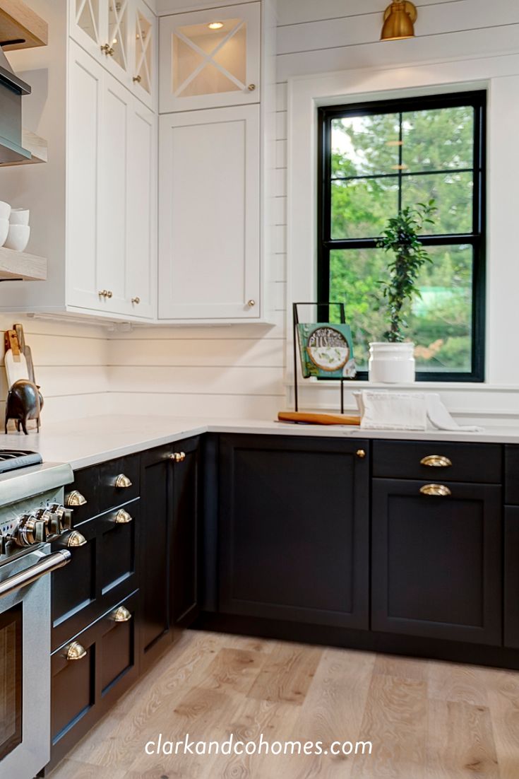 Black Windows And Lower Base Cabinets Accent The Upper White Cabinets And S White Farmhouse Kitchens Kitchen Cabinets Black And White Modern Farmhouse Kitchens