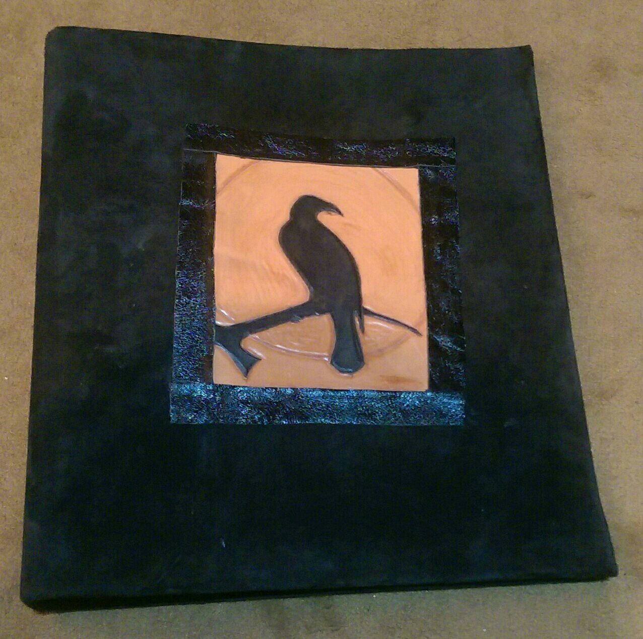 A folder for sheet music, covered in black sheep skin. The raven on the tree was carved and partially dyed.