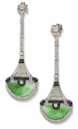 A pair of enamel, jade and diamond pendant earrings. Each designed as a highly stylised pagoda, with carved jade base and black enamel overhanging storey, supporting an articulated tapering tower surmount pierced and millegrain-set throughout with old brilliant and rose-cut diamonds and black enamel detail,  later post fittings. Age unknown, but in the Art Deco style.