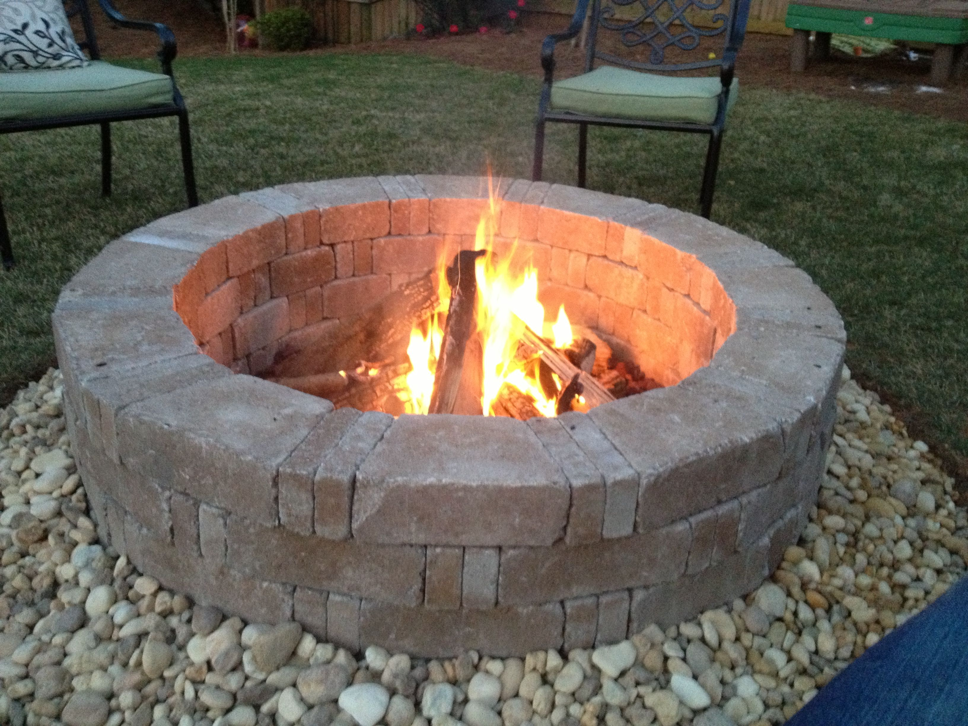 Rumblestone firepit with river stone surround and red lava