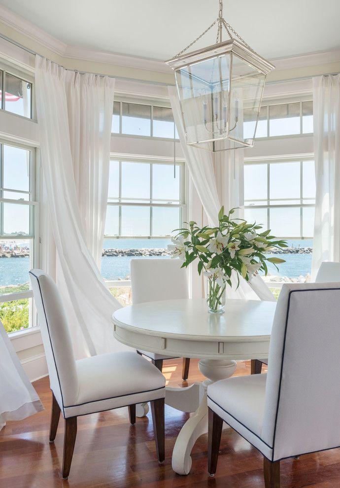 white coastal dining room, sheer curtains, bay window, round white