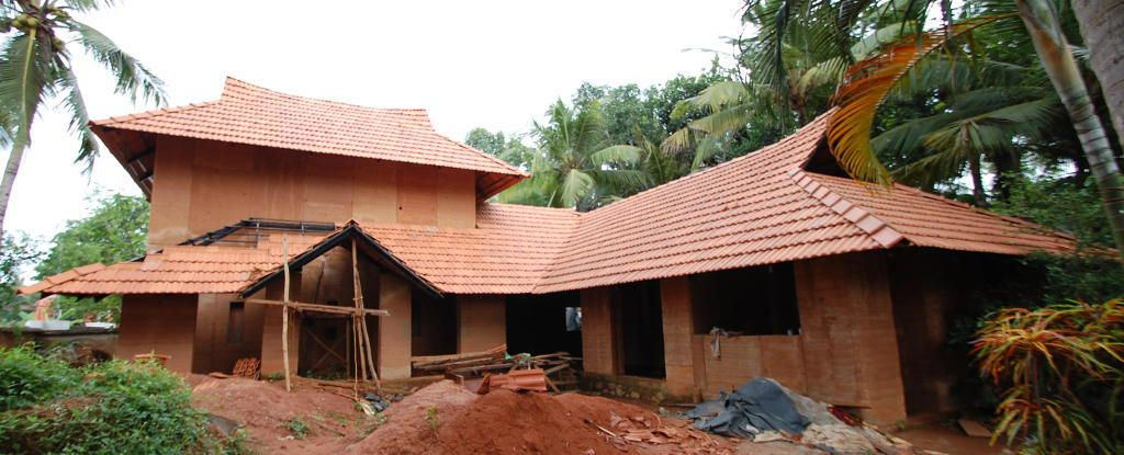 Rammed earth building under construction at kerala india for Adobe construction cost