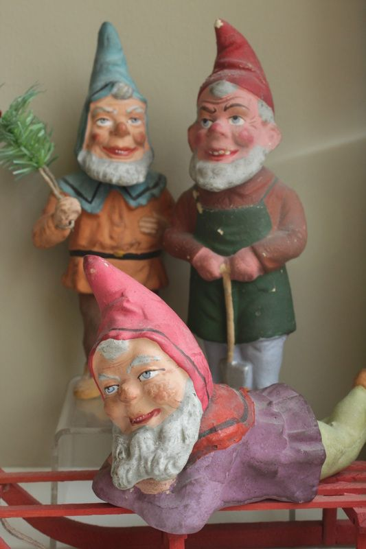Here is a rare grouping of German papier-mache elves (Wichtelmaenner), each one a candy container.  One holds a feather tree sprig, another has on his work apron holding a shovel, and the one in the foreground is resting on a red wooden sleigh.   Great detail in the faces and clothing of the molds used to create the candy constainers, as well as brightly colored clothing with hand painting.  Ca. 1900.