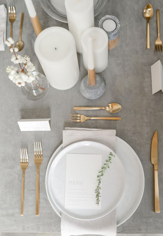 a minimalist wedding table setting with a grey tablecloth, gold cutlery and white candles looks ethereal #whitecandleswedding