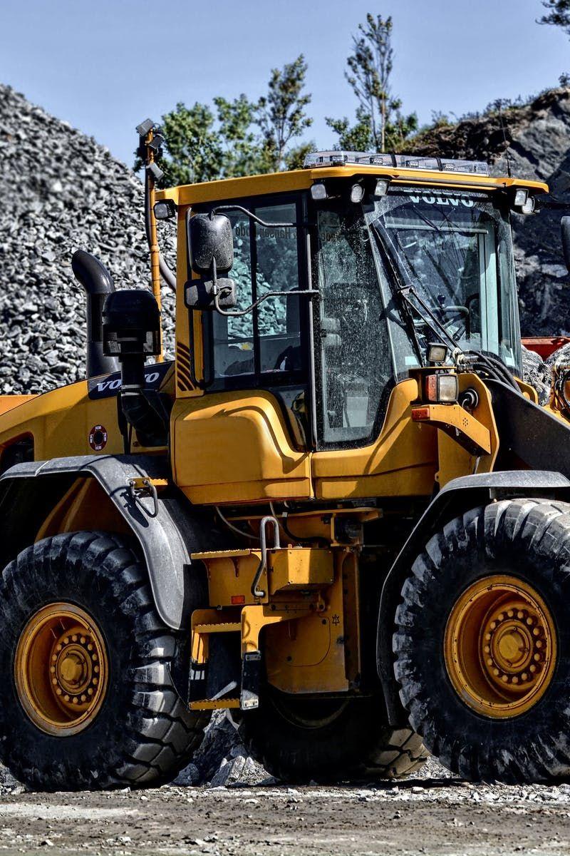 Orange and Black Tractor Next to Piles of Rocks | Confianz | Pinterest
