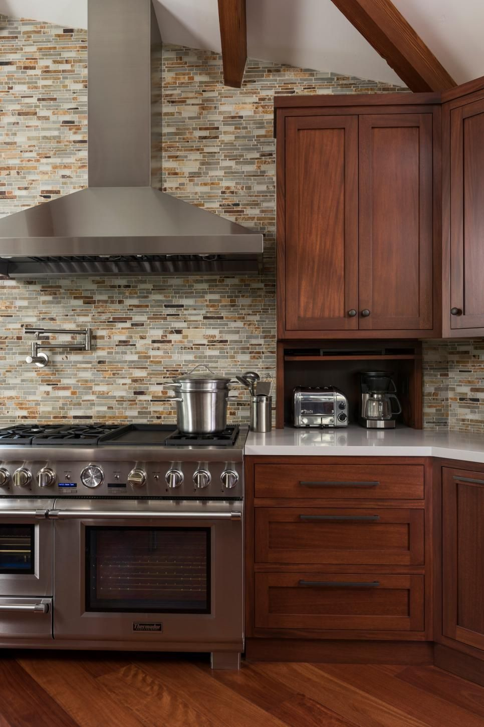 Warm brown cabinets and hardwood floors contrast against the sleek ...