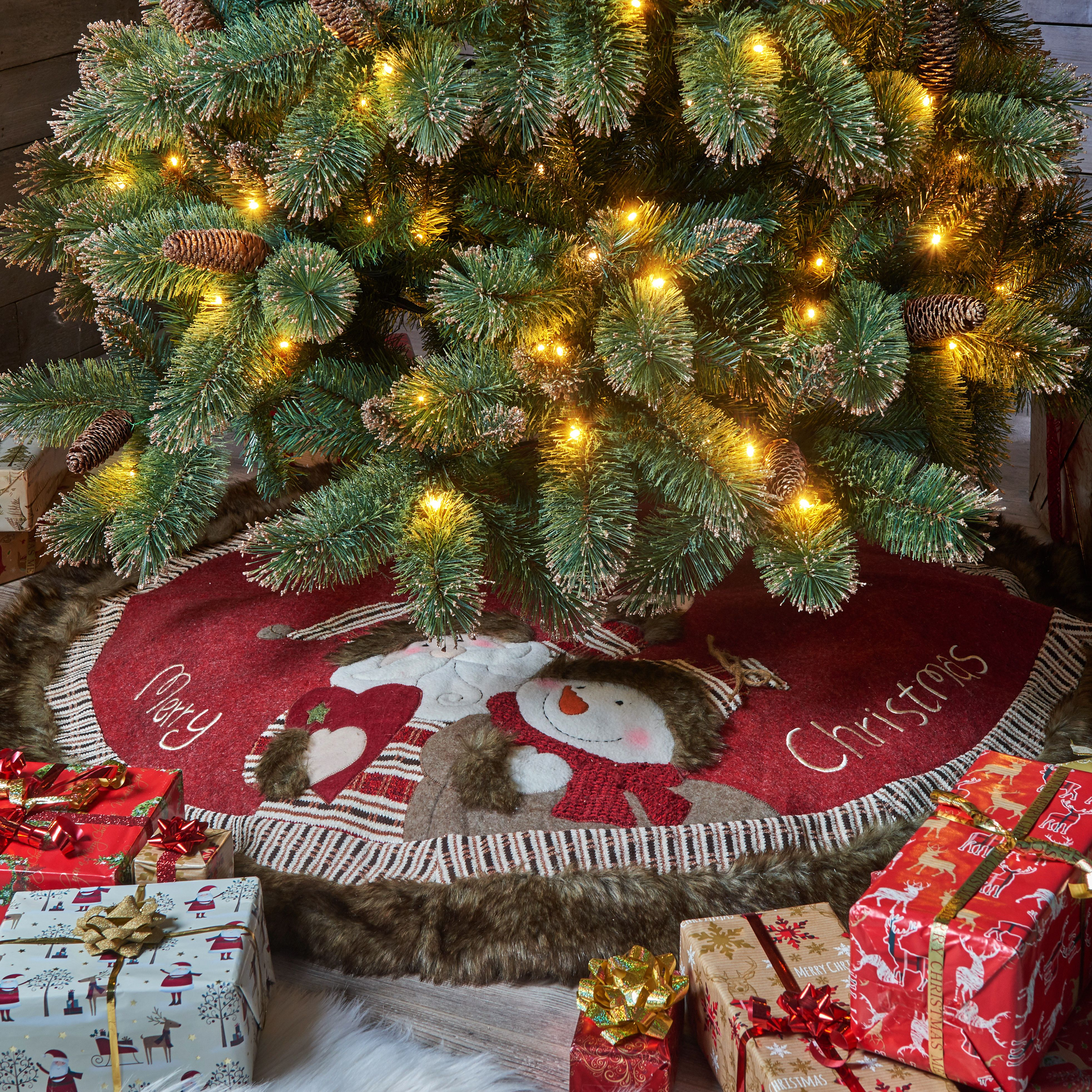 With a charming tartaned trim, the Merry Xmas Tartan Santa