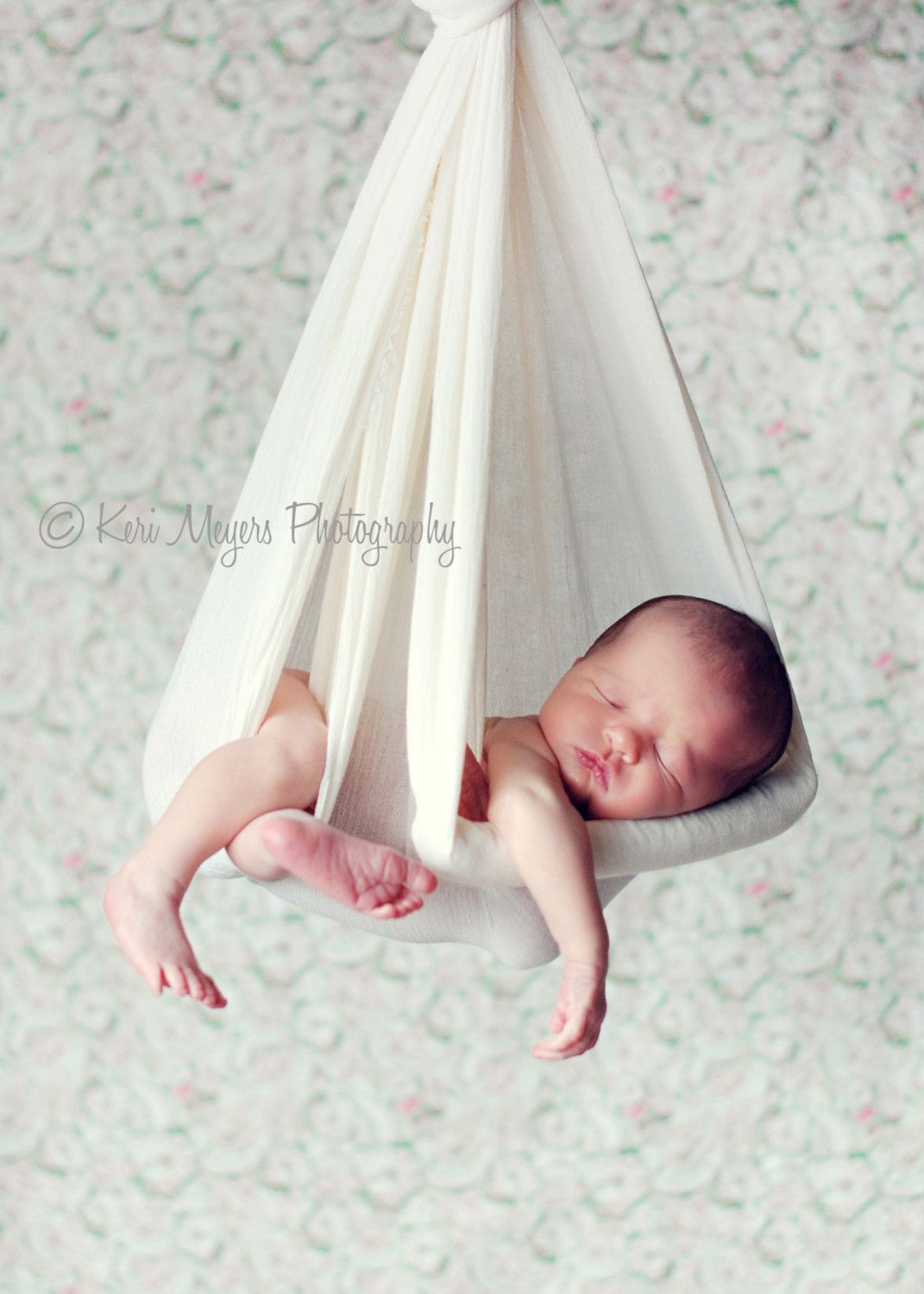 newborn hanging in cheesecloth bundle