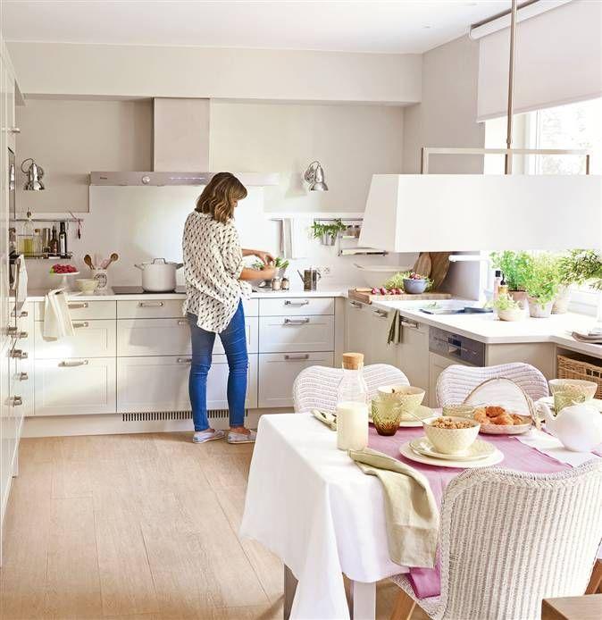 Mujer en cocina con office con forma de L en blanco, con armarios