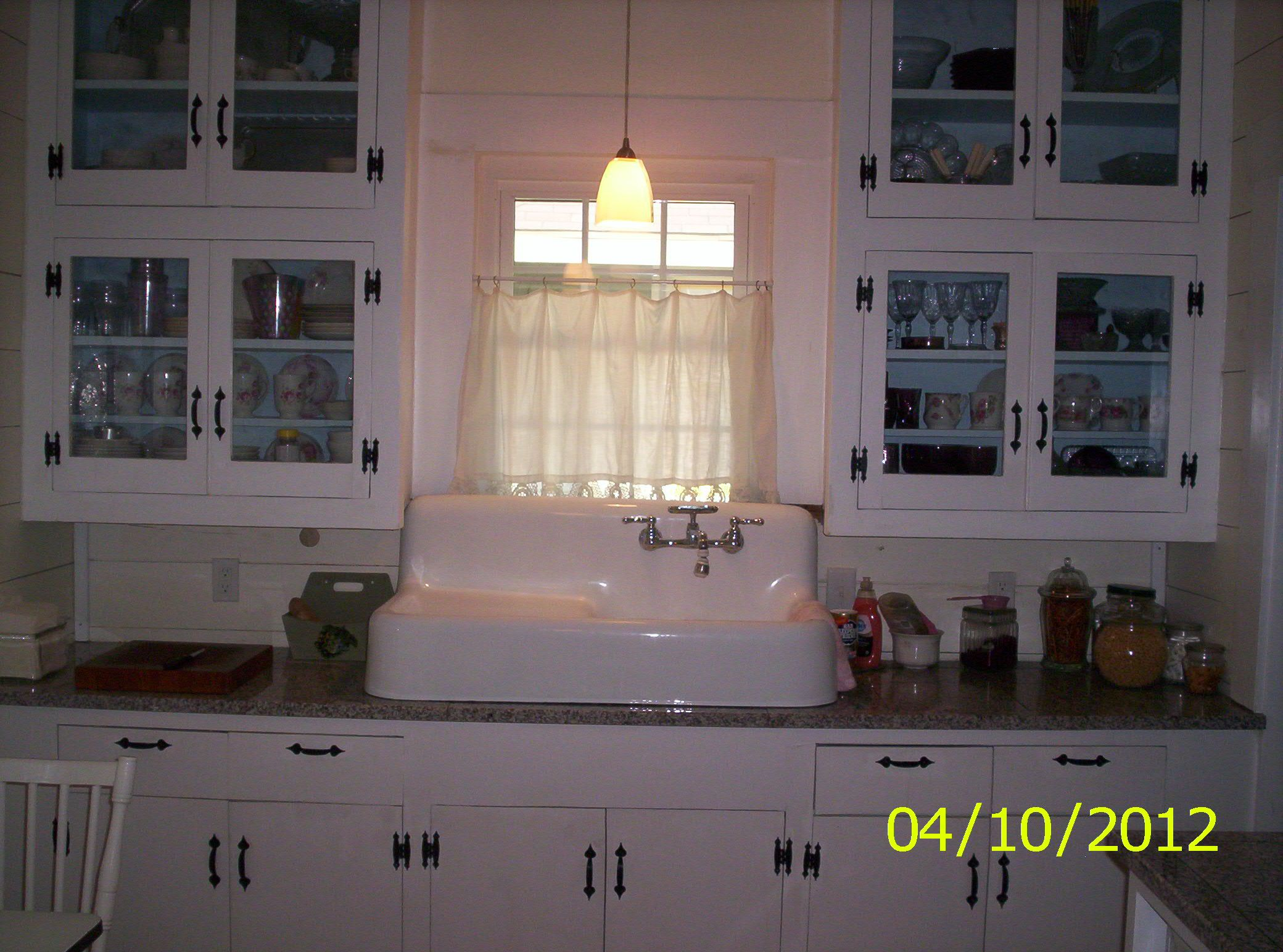 Kitchen sink is new but of vintage design.  This bank of cabinets are original to the 1926 house. The solid center wood door panels were cut-out and replaced with glass. The inside of the cabinets were painted an intense blue which really makes the white china pop. Modern cased glass pendant lighting is from Lowe's