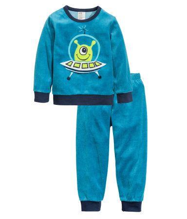 En tvådelad pyjamas i mjuk velour med kontrastfärgade muddar. Långärmad tröja med broderat motiv fram. Byxa med resår i midjan och mudd vid benslut.