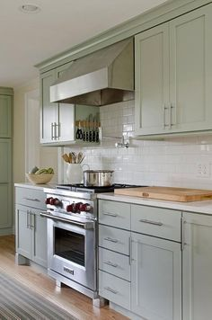 Soothing Green Kitchen Features Sage Green Cabinets Paired With White Quartz  Countertops And A White Subway Tiled Backsplash.