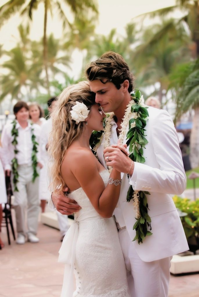 The bride and groom looked stunning in their all-white attire and Hawaiian accessories. Kelly wore a flower in her hair, while Keith wore a white lei and a traditional Maile lei. Photograph by: Stewart Pinsky Photography