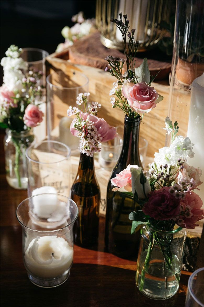 DIY wedding decor - brown bottlles in different sizes and glass jars filled in with flowers #weddingdecor