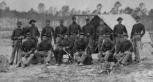 3rd Indiana Cavalry: a number of styles of hats worn by Federal soldiers during the Civil War. A soldier, second from left on the back row, wears the brimmed, wool felt hat was common for both officers and male civilians of the time. A soldier, second from right in back row, wears a softer, less-constructed version of same hat that was more popular with farmers and other laborers of the day. Other men wear variations on the hat that is most closely associated with the Civil War, the billed…
