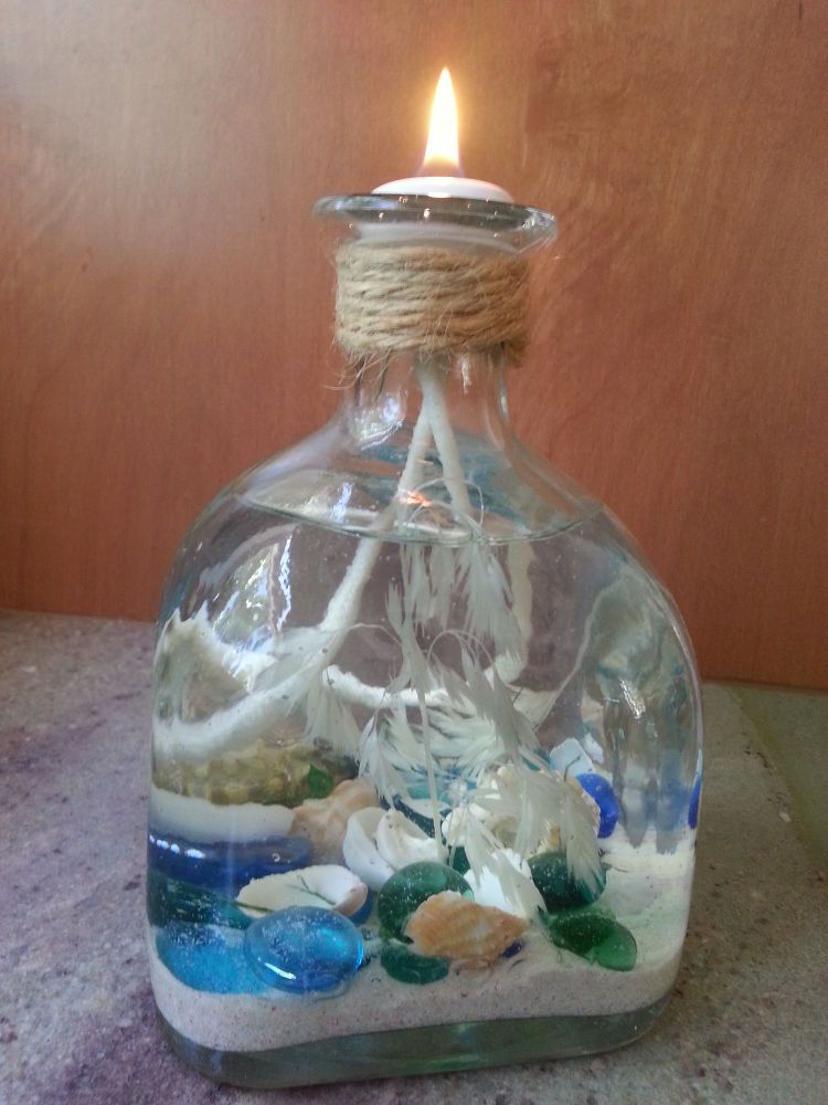 She pours sand into an empty liquor bottle and a few steps for Glass bottle crafts to make